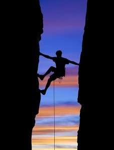 Rock climber reaching across a gap
